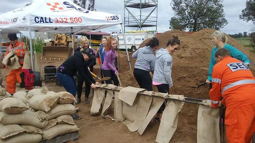 Local residents assist SES volunteers in filling sand bags in Forbes. (AAP)