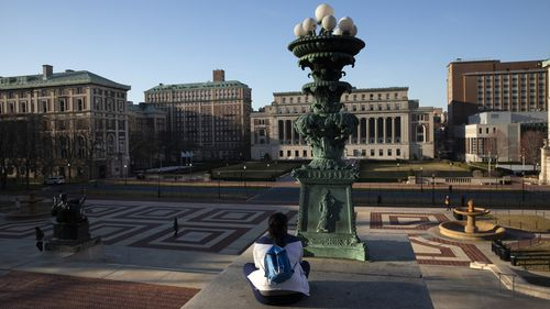A woman sits on the Columbia University campus, Monday, March 9, 2020 in New York.