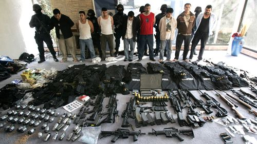 Men arrested by Mexican federal police stand behind weapons found in a home in Mexico City in 2008. Eleven alleged hit men working for the Sinaloa drug cartel were captured at two Mexico City mansions stocked with grenades, automatic weapons and body armour.