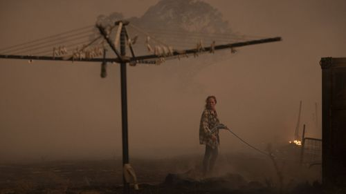 Clair Cowie defends her home from an out of control spot fire on February 01, 2020 at Bredbo North near Canberra,