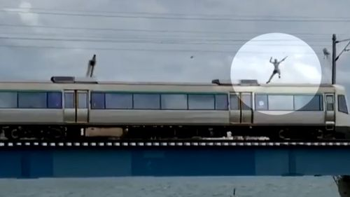 The man can be seen balancing on the train, even waving to the camera before making the horrifying jump. (Facebook)