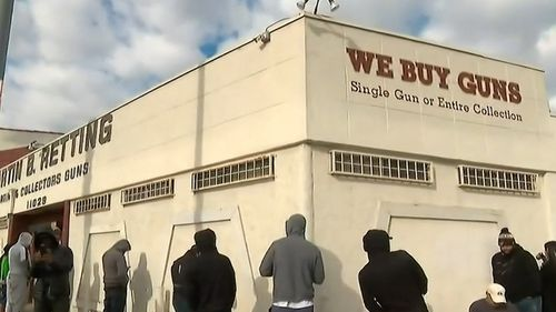 People in hooded sweatshirts wait in line outside an LA gun shop.