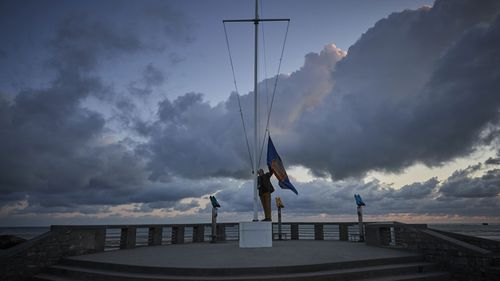 Adrian Cox, a British Expat and Councilor of Arromaches, raises the flag of the Normandy Veterans Association at dawn to commemorate the 76th Anniversary of the D-Day landings at dawn on Gold Beach on June 06, 2020 in Arromanches-les-Bains, France
