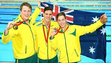 Australian gold medallist Mitch Larkin poses with silver medallist Josh Beaver (right) and bronze medallist Matson Lawson (left) after the medal ceremony for the men's 200m backstroke.