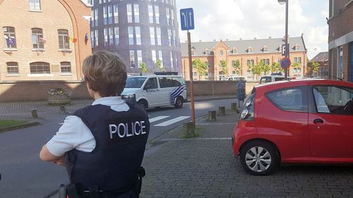 A police officer stands guard close to a police building in Charleroi. (AFP)