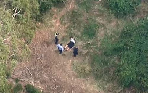 One of the two men arrested is handcuffed by police in Daylesford. (9NEWS)