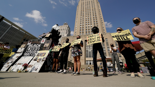 Protesters hold signs outside city hall Thursday, Oct. 8, 2020, in Kansas City, Mo. Protesters have occupied the lawn and plaza in front of city hall for more than a week demanding the resignation of police chief Rick Smith and an officer who knelt on the back of a pregnant woman while arresting her last week. (AP Photo/Charlie Riedel)