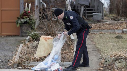 A police officer investigates outside a house on Mallory Crescent in Toronto, where Bruce McArthur did landscape work.