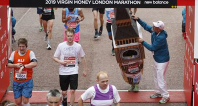 Mr Bates is helped by an official as he attempts to get past the finishing line, during the 39th London Marathon in London, Sunday, April 28, 2019.