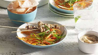 Chicken satay with pressed rice, peanut sauce and carrot salad