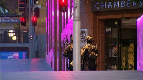 Night falls over Martin Place, as a captor holds hostages at gunpoint. (9NEWS)