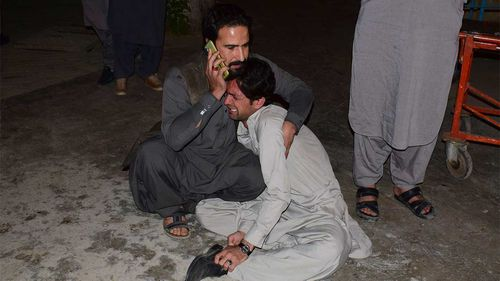 A Pakistani man comforts to another mourning over the death of his family member in a bomb blast, at a hospital in Quetta.