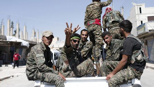 Members of YPG flashing victory sign after coming from Syrian town of al-Raqqa, in Syria. (AAP)