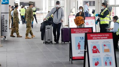 Returning overseas travellers walk towards waiting buses at Sydney Airport to take them to quarantine hotels.