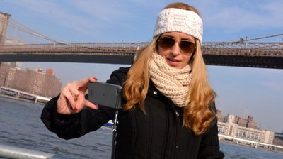 "This unidentified woman's earned the title of ""world's most selfish selfie"" in December 2013 for snapping a photo in front of a suicidal man about to jump off New York's Brooklyn Bridge . (Paul Martinka)"