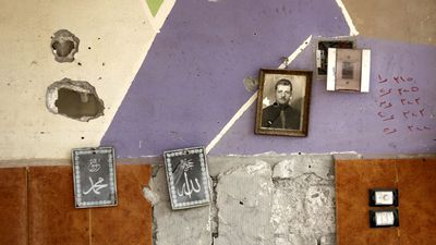 Photos on the wall of a bullet-scarred home.