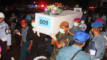 Indonesian military personnel carry coffins containing the body of the victims of AirAsia Flight 8501. (AAP)