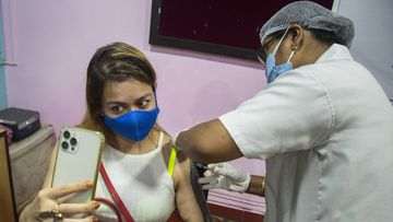 A woman takes selfie as she receives the Covishield vaccine against COVID-19 in Gauhati, Assam, India.