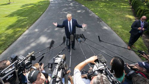 Donald Trump speaks to reporters outside the White House.