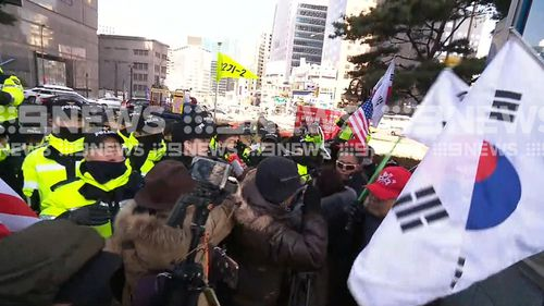 South Korean flags flew during the protest. Athletes from the North and the South will march under a unified flag at the Games. (9NEWS)