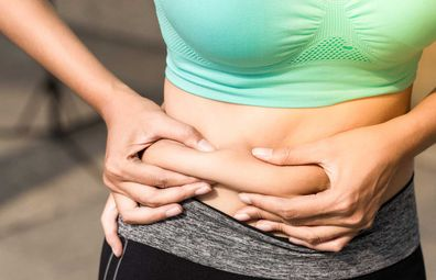 Woman in active wear pinching stomach