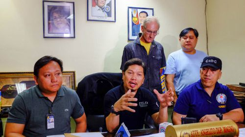 Peter Gerard Scully stands behind investigators from the National Bureau of Investigation. (Source: Rappler)