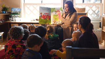 A teacher at a Sydney child care centre reads to young children.