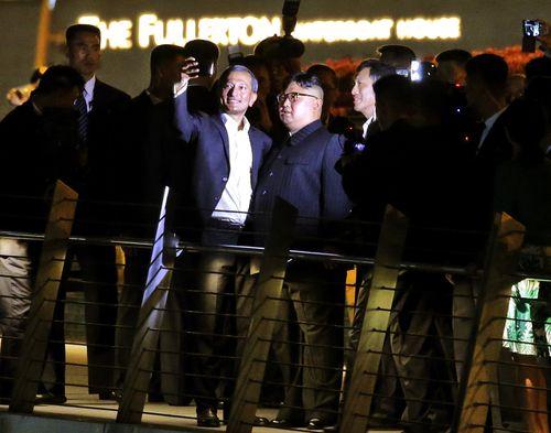 Kim Jong-un and Singapore Foreign Minister Vivian Balakrishnan (left) take selfies on the Jubilee bridge. Picture: AAP