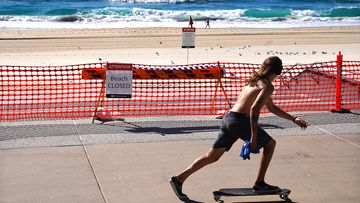 A skateboarder passes a closed section of Surfers Paradise Beach on the Gold Coast