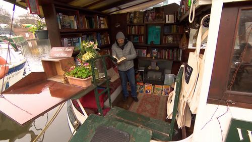 Jon Privett inside his floating bookstore. (9NEWS)