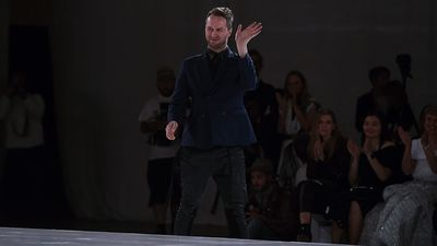 Designer Toni Matecevski gestures to the audience at the completion of his show (AAP)