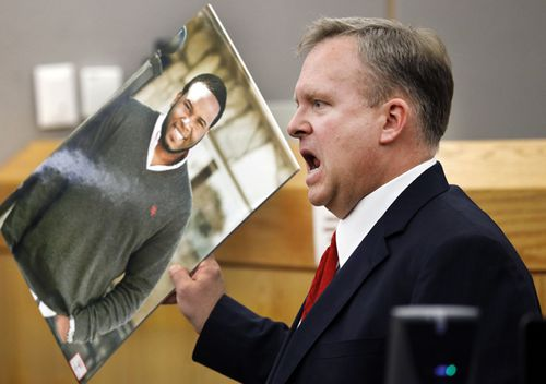 Assistant District Attorney Jason Hermus waves a photo of Botham Jean at the jury as he presents his closing arguments in Amber Guyger's murder trial in the 204th District Court at the Frank Crowley Courts Building in Dallas. Guyger shot and killed Botham Jean, an unarmed 26-year-old neighbour in his own apartment last year. She told police she thought his apartment was her own and that he was an intruder.