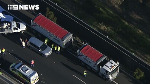 The collision involved a motorcycle and two trucks. (9NEWS)