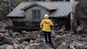 A firefighter walks among the rocks and mud left by a mudslide yesterday. (AAP)