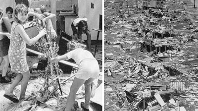 Some children pull their Christmas tree from the rubble and try to reerect it. Right: A photo taken in June 1975 shows homes remain flattened. (AAP)