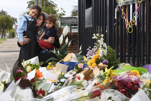 A mother and her young children place flowers outside the Banksia Road Public School in Greenacre. (AAP)