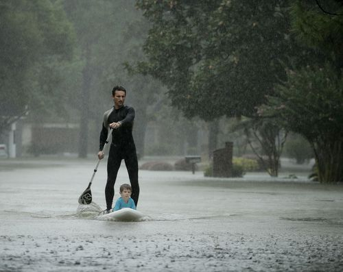 Alexendre Jorge evacuates Ethan Colman, 4, from a neighbourhood inundated by floodwaters in Houston. (AP)