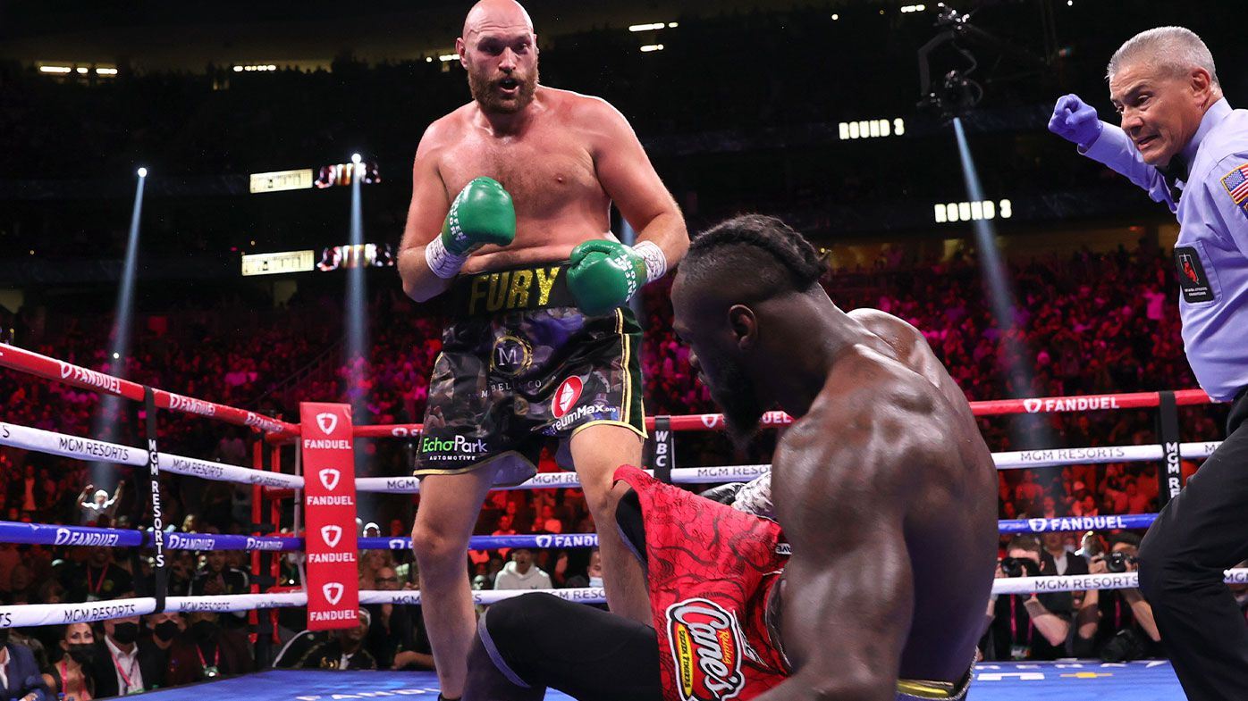 Tyson Fury (L) knocksdown Deontay Wilder (R) during their fight for the WBC heavyweight championship
