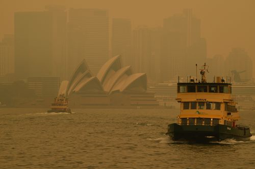 A ferry passes the Sydney Opera House as smoke haze from bushfires in New South Wales blankets the CBD in Sydney, Thursday, December 19, 2019.