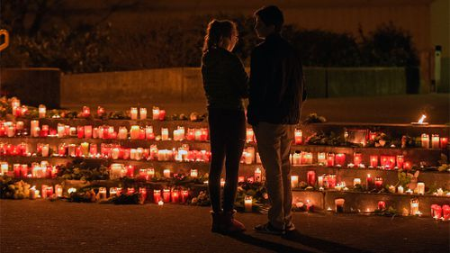 Students stand in front of candles in front of the Joseph-Koenig Gymnasium in Haltern, western Germany. (AAP)