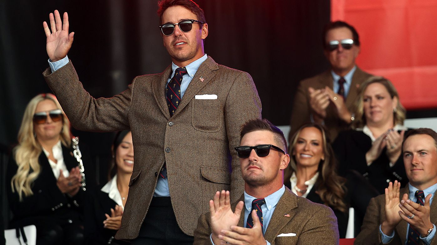 Brooks Koepka acknowledges the crowd at the Ryder Cup opening ceremony while a stony faced Bryson DeChambeau looks on.