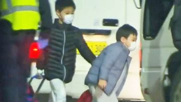 Two children board a Qantas flight in Wuhan, headed for Darwin.