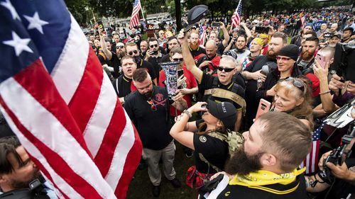 Members of the Proud Boys and other right-wing demonstrators plant a flag in Tom McCall Waterfront Park during a rally in Portland, Oregon.