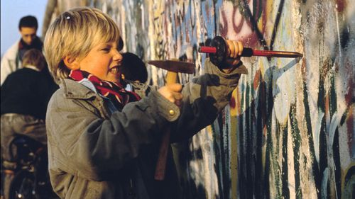 A boy chips at the Berlin wall on November 12, 1989 in Berlin, Germany.(Photo by Pool CHUTE DU MUR BERLIN/Gamma-Rapho via Getty Images)