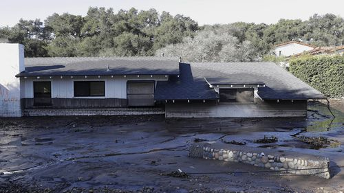 A home sits in mud and water in Montecito on Wednesday. (AAP)