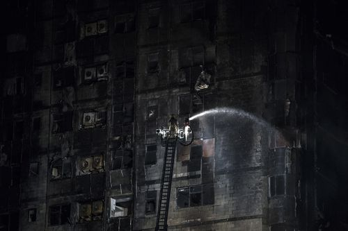A firefighter douses the  Abbco Tower in Sharjah, after a huge blaze ripped through the building.