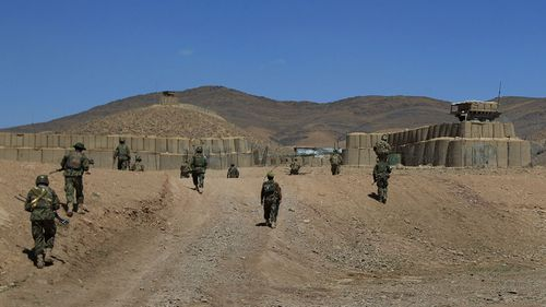 In this 2012 file photo, Australian troops enter Patrol Base Wali after a patrol with Afghan National Army soldiers in the Mirabad Valley, Afghanistan.