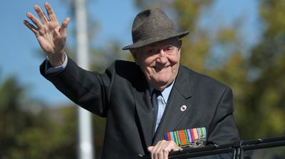 A veteran waves as he makes his way towards the Shrine of Remembrance in Melbourne. (AAP)