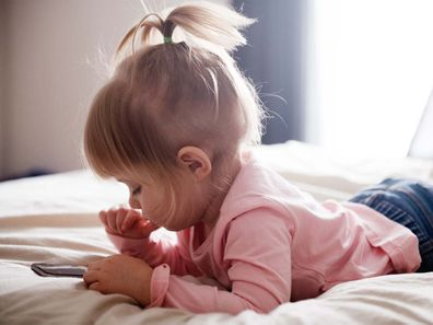 Toddler using a phone while lying on her stomach in bed
