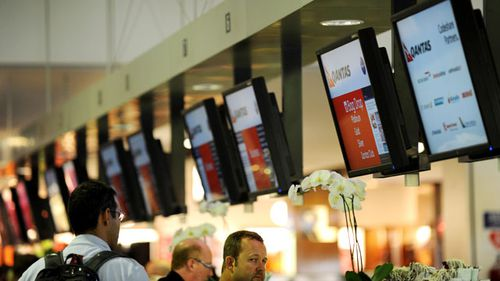 Qantas passengers check in at Sydney International Airport in Sydney. (AAP)